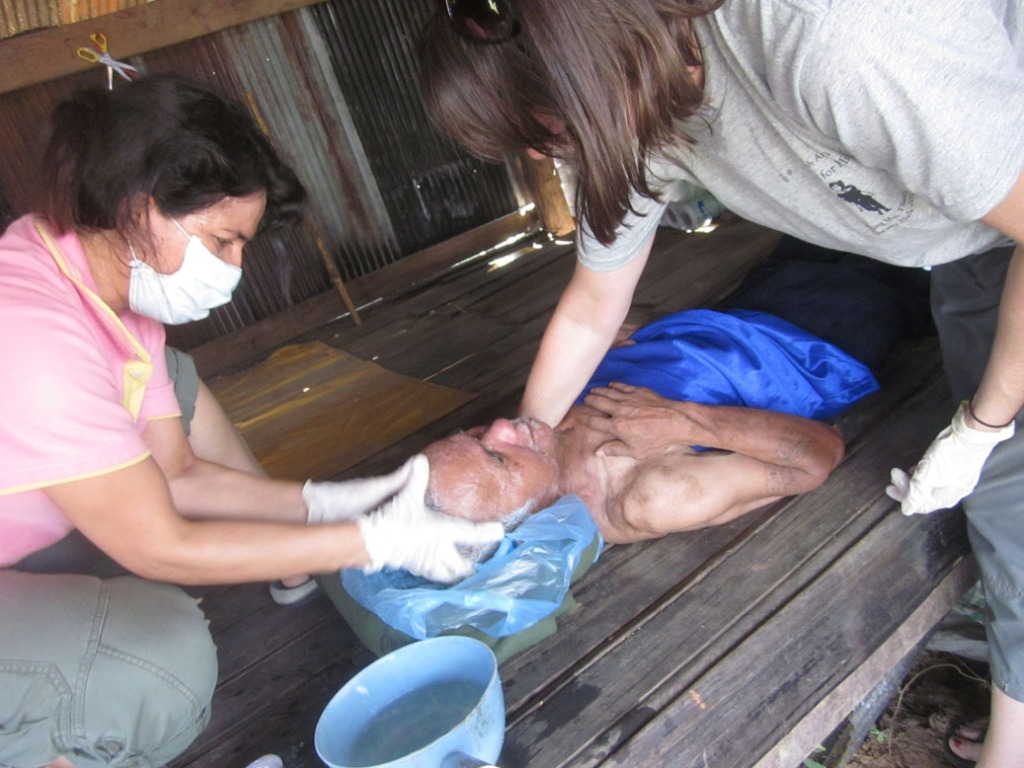 Our staff caring for a poor, handicapped homeless man from Burma.